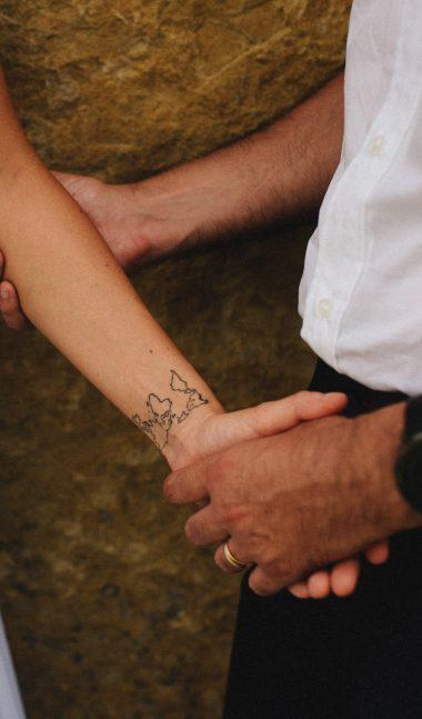 Младоженец държи булката си за ръката