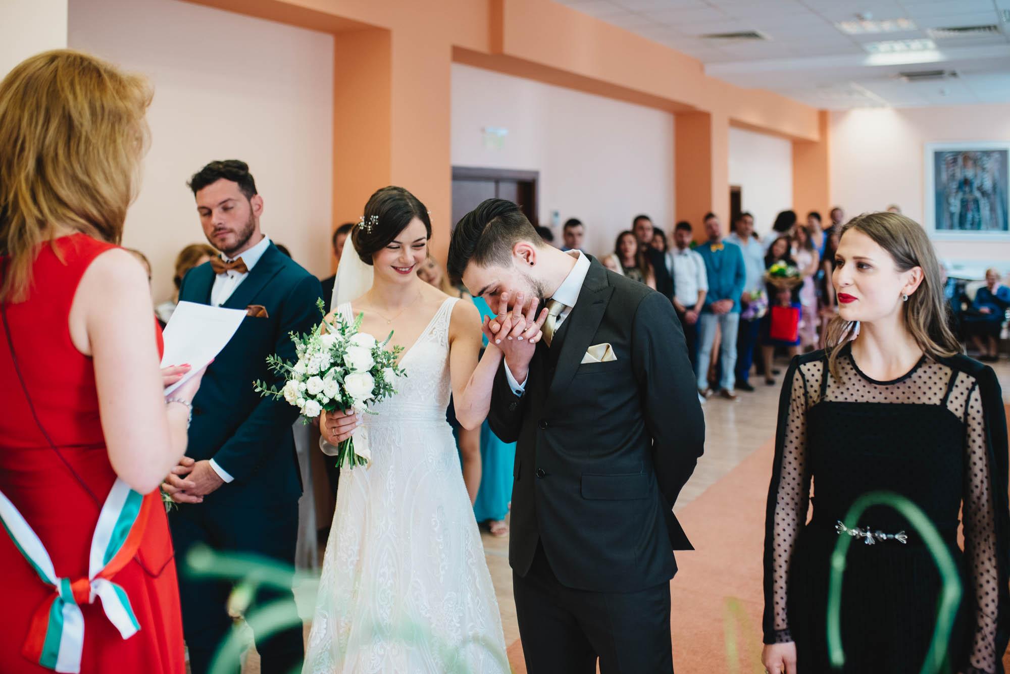 Младоженецът целува ръката на булката по време на гражданския ритуал